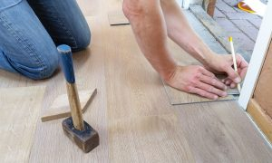man installing floor and beside him is a hammer