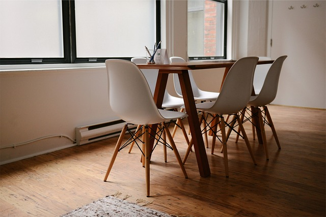 wooden floor in office with white chairs and wood table